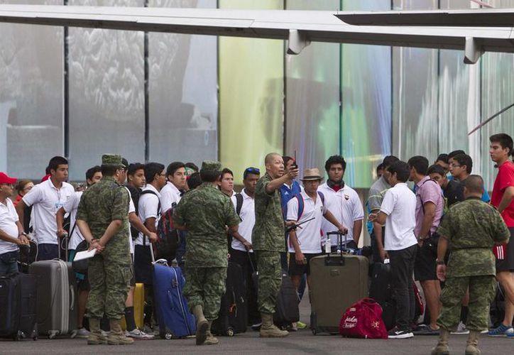 En la imagen, turistas llegan a un hangar de la Fuerza Aérea en la Ciudad de México después de ser evacuados vía aérea por las fuerzas armadas de la zona devastada por el huracán Odile en Los Cabos, Baja California Sur. (Agencias)