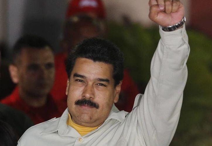 El presidente de Venezuela Nicolás Maduro sostiene su puño en alto durante un acto en el palacio presidencial de Miraflores en Caracas. (AP)