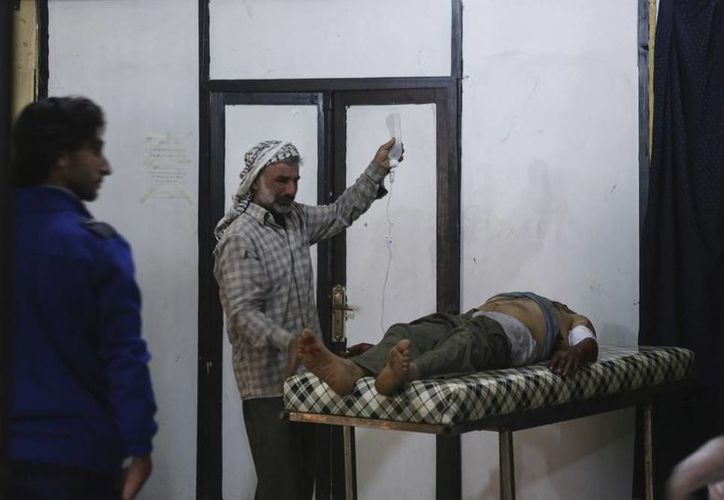 Un hombre sujeta una bolsa de suero junto a un herido que recibe tratamiento médico en el hospital de campaña tras el ataque.  (EFE/Archivo)