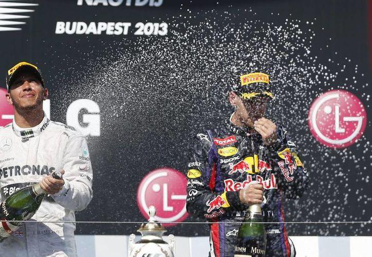 Lewis Hamilton (i) festeja su triunfo en Hungría, le acompaña Sebastián Vettel, quien llegó en tercero. (Agencias)