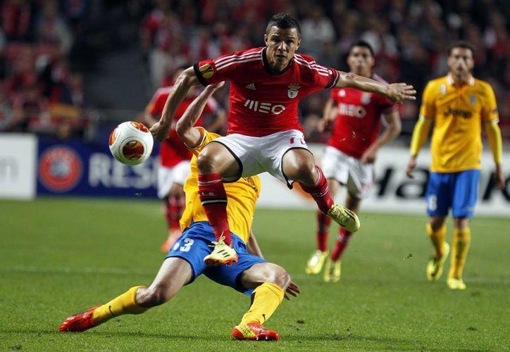 Lima, uno de los anotados por Benfica, salta ante la barrida enérgica de Giorgio Chiellini, de Juventus. (Foto: AP)