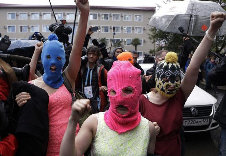 Las integrantes del grupo Pussy Riot, Nadezhda Tolokonnikova, con el pasamontañas azul, y Maria Alekhina, con el rosado salen tras ser liberadas de una comisaría de policía del distrito Adler de Sochi, Rusia. (EFE)