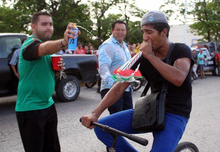 Dos de los detenidos festejando la victoria de la Selección Mexicana. (Sergio Orozco/SIPSE)