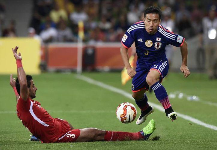 El nipón Nagatomo (d), evita la barrida de Tareq Khattab, en partido que Japón ganó a Jordania dentro de la Copa de Asia. (Foto: AP)