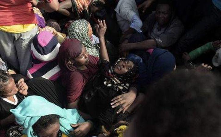 Una mujer se desmaya mientras espera ser rescatada en el Mar Mediterráneo. (AFP/Milenio)