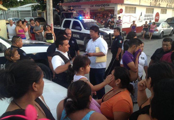 """En la imagen """"El Gordo"""" dialoga con los agentes, mientras sostiene las copias en sus manos. (Ángel Mazariego/SIPSE)"""