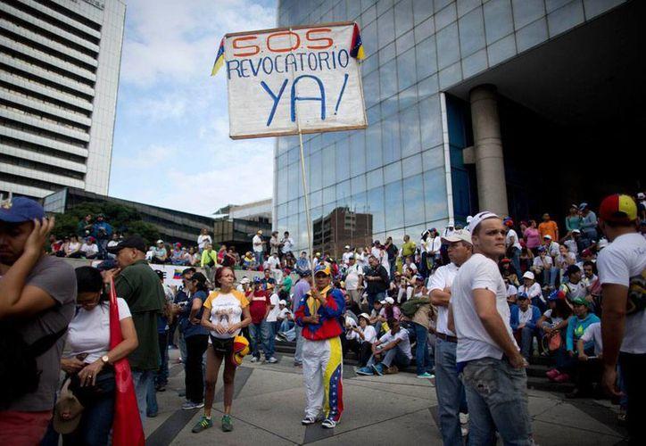 Un hombre sostiene un cartelón en el que exige el referendo revocatorio, durante durante una reunión previo a la marcha en Caracas, Venezuela, el 1 de septiembre de 2016. (AP/Ariana Cubillos)