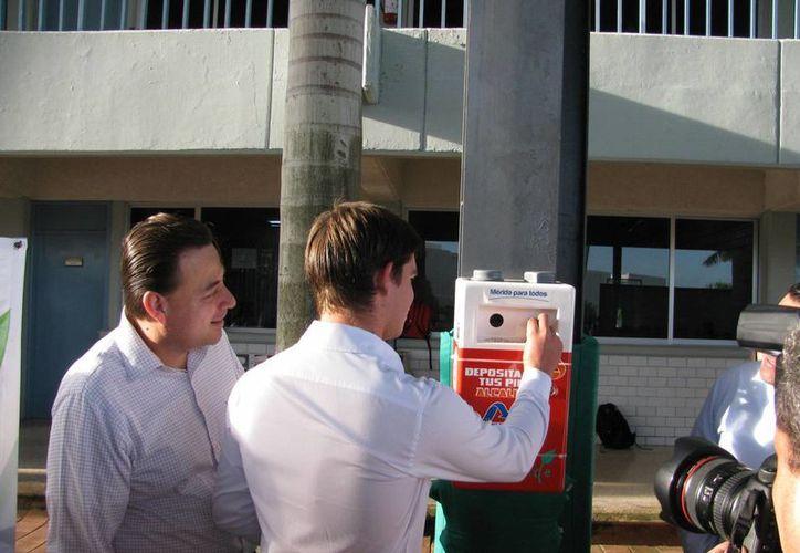 Ciudadanos depositan pilas en un módulo instalado para recibir las baterías y darles una adecuada disposición final. (SIPSE)