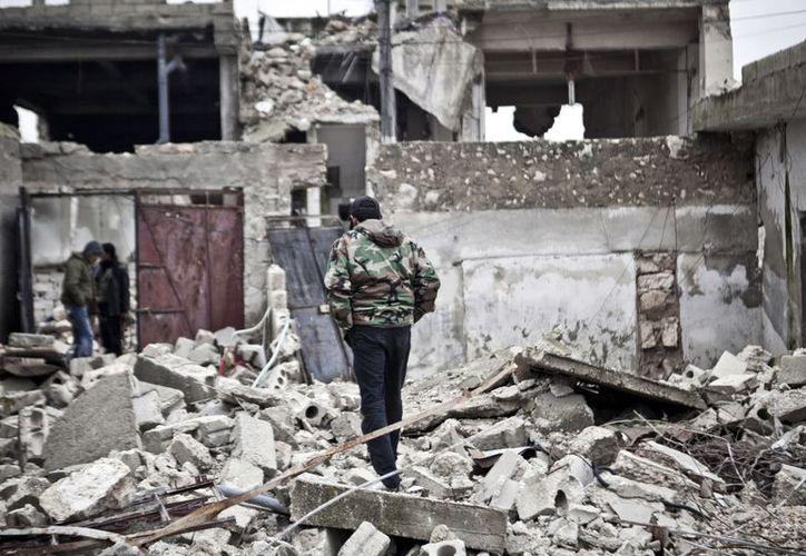 Combatientes sirios 'libres' caminan entre las ruinas de un pueblo. (Agencias)