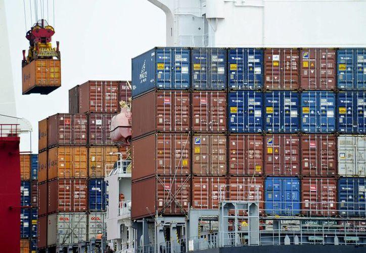 Imagen del 5 de agosto del 2010 muestra un contenedor cargado hasta un barco mercante en el puerto de Tianjin en China. Los consumidores y negocios estadounidenses pagarían si el presidente electo Donald Trump cumple su promesa e impone altos impuestos a importaciones provenientes de China y México. (AP/Andy Wong, Archivo)