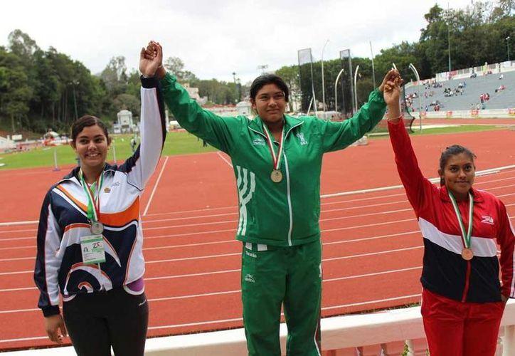 La lanzadora yucateca Arleth Flores, alegre y en lo más alto del podio por la medalla de oro conseguida en la Olimpiada Nacional. (Milenio Novedades)