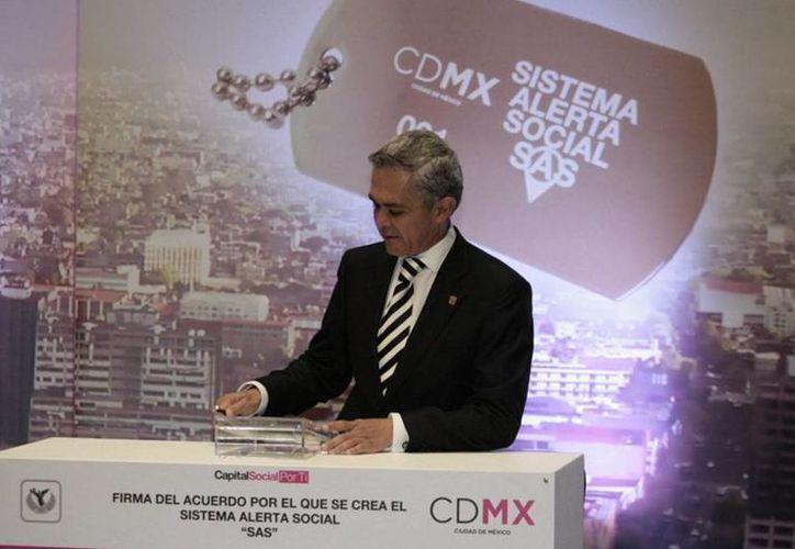 El jefe de Gobierno del DF, Miguel Ángel Mancera, tras firmar este miércoles el acuerdo para crear el Sistema de Alerta Social (SAS). (twitter/@ManceraMiguelMX)
