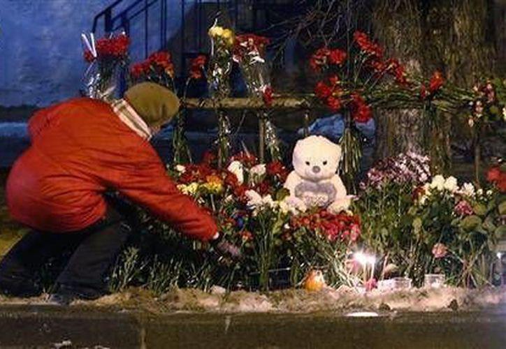 Una mujer coloca flores frente a los restos de un trolebús en Volgogrado, Rusia, el martes 31 de diciembre. (Foto AP/Denis Tyrin)