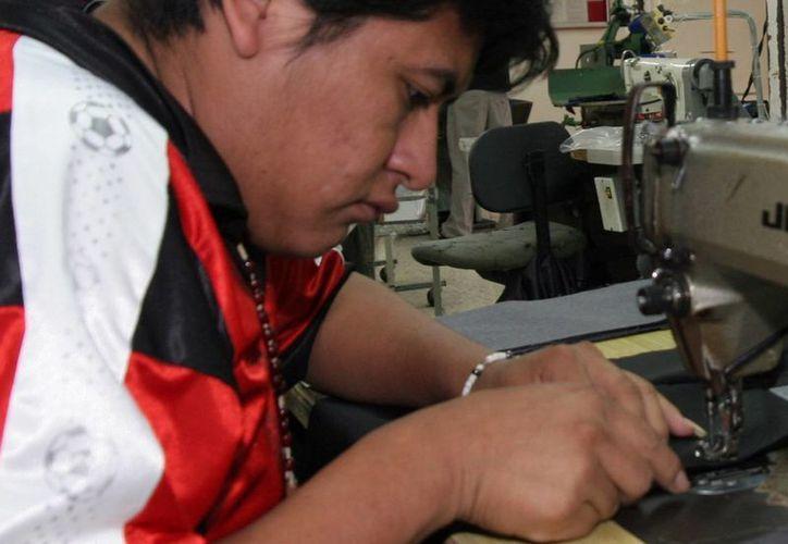 Industrialmente Yucatán ha tenido un crecimiento porcentual del 7.9. Imagen de contexto de un joven en una fábrica de ropa.  (Milenio Novedades)