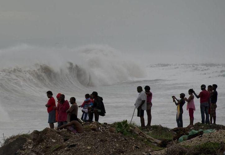 Algunos curiosos cubanos observan los efectos del huracán Matthew en la costa este del país. Se espera que el fenómeno avance rumbo a la costa de Estados Unidos. (AP/Eduardo Verdugo)