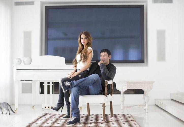 Gilbert Chikli, de 50 años, y su esposa Shirly Chikli, de 31, posan para una foto en su casa de Ashdod, Israel. Chikli estafó a algunas de las empresas más grandes del mundo y luego blanqueó millones en China. (Agencias)