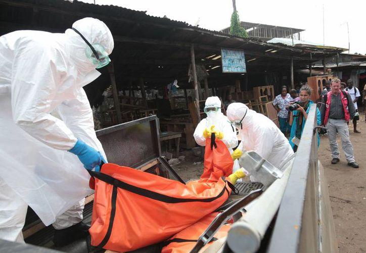 Trabajadores de la Salud, colocan un cuerpo infectado con el virus del ébola sobre un vehículo, en Monrovia, Liberia. (Notimex)