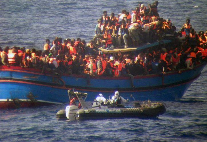 Fotografía cedida por la marina de Italia hoy que muestra una lancha aproximándose a un barco del que varios inmigrantes fueron rescatados entre Sicilia y el Norte de África ayer. (EFE)