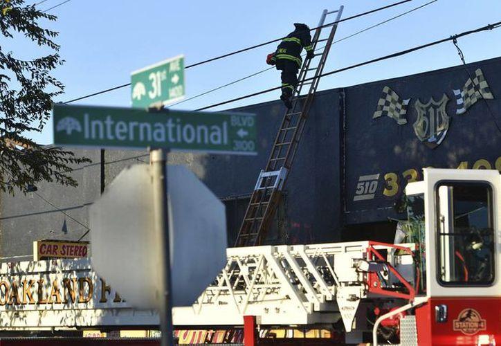 Bomberos examinan el lugar donde hubo un incendio en un almacén donde se realizaba una fiesta el sábado en Oakland, California. (AP/Josh Edelson)