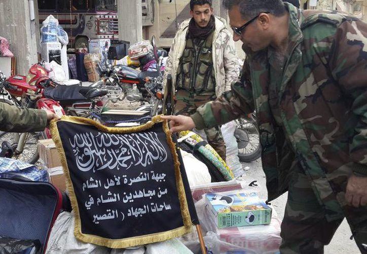 Soldados del ejército sirio muestran una bandera perteneciente al Frente Jabhat Al Nusra, organización vinculada a Al Qaeda. (Archivo/EFE)