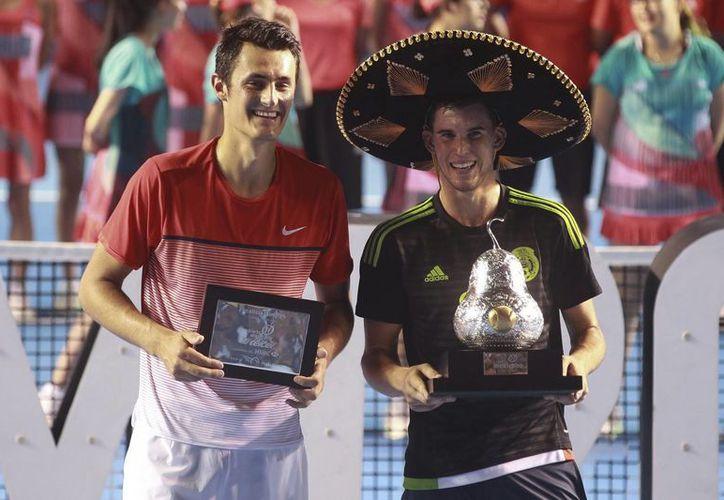 El tenista austríaco Dominic Thiem (d) y el australiano Bernard Tomic (i), posan con sus respectivos trofeos de primer y segundo clasificado, tras disputar la final del Abierto Mexicano de Tenis celebrada el sábado en Acapulco, México. (EFE)