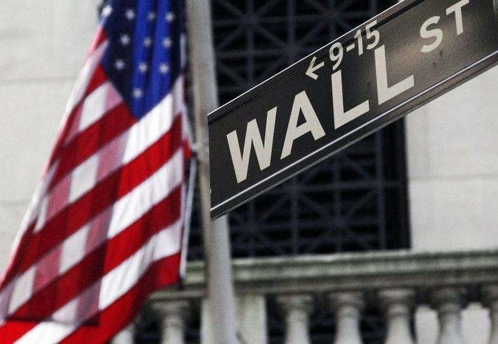 Imagen de archivo que muestra una bandera estadounidense en Wall Street, afuera de la Bolsa de Valores de Nueva York, EU, amenazada por el colectivo Anonymous. (Archivo/AP)