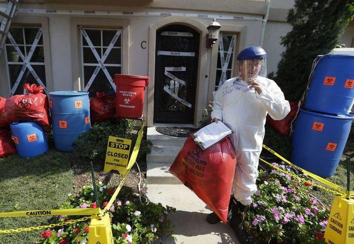 """Para complementar el ajuar James Faulk viste un traje de protección con la etiqueta de """"pasante de CDC"""" y una careta. (AP)"""