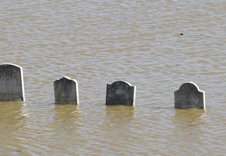 Varias lápidas se asoman en la superficie tras una inundación en el cementerio Marysville en Marysville, California, este sábado. La inundación del cementerio provino del río Feather. Las lluvias de varios días causaron el desbordamiento de ríos y obligaron a que se utilizara por primera vez un canal de emergencia en la presa de Oroville. (AP Foto/Rich Pedroncelli)