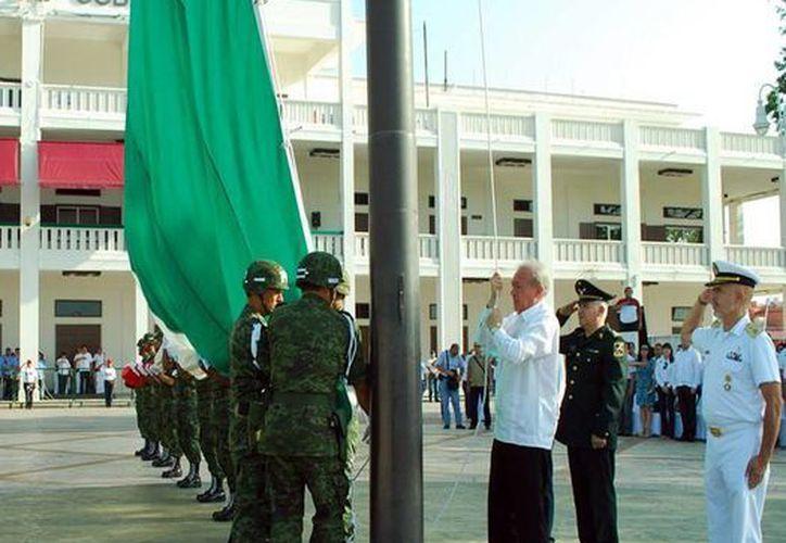 El izamiento de la bandera monumental en la Plaza Cívica del Parque Central de Chetumal, ubicado frente a Palacio de Gobierno. (Redacción/SIPSE)