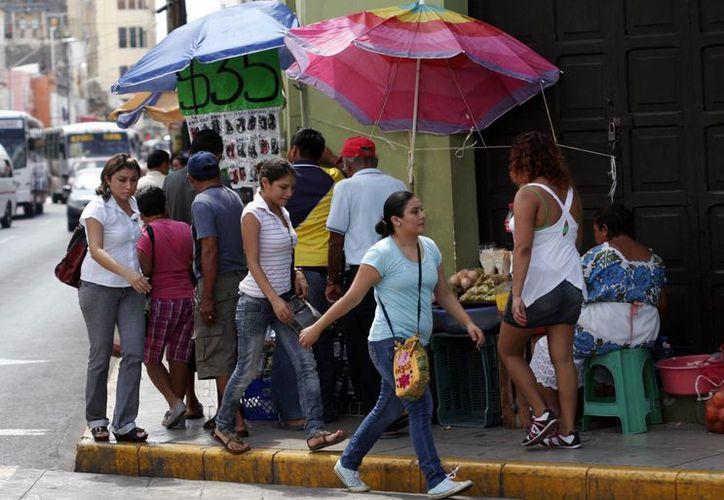 Los puestos informales ocupan gran espacio de las banquetas del centro de Mérida, lo que obstaculiza el paso. (Milenio Novedades)