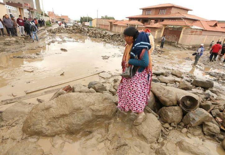 Una mujer intenta pasar el lodazal en Tiquipaya, que fue afectada por una mazamorra la noche del martes. (Foto: APG)