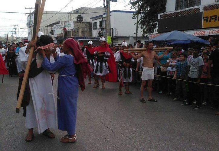 Varias personas participan sosteniendo una cuerda de varios metros alrededor de las actores del vía crucis del parque de la Rehoyada. (Stephani Blanco/SIPSE)