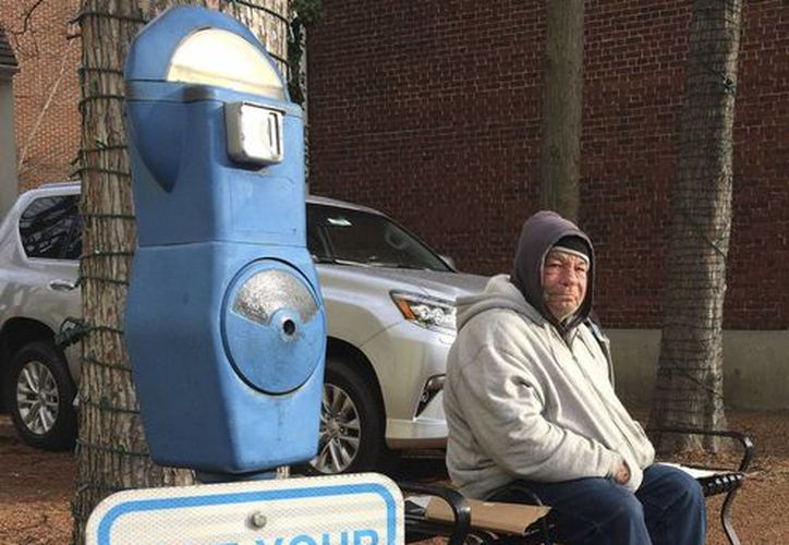 Un indigente que dijo llamarse Joe Drury descansa cerca de un parquímetro habilitado para recibir limosnas para los indigentes, en Annapolis, Maryland, el martes 27 de diciembre de 2016. (AP Foto/Pat Eaton-Robb)