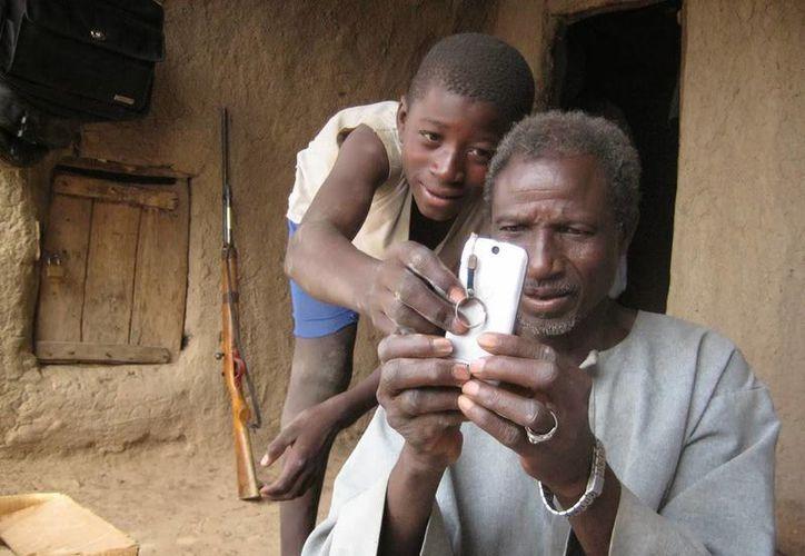 Los teléfonos Android que se venderán en África son modelos sencillos que no podrán hacer muchas de las funciones que tienen los aparatos más caros. Imagen de un hombre que utiliza un teléfono celular con la asistencia de un chico. (Archivo/AP)