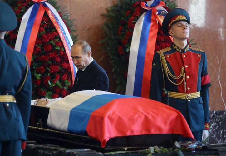 El presidente Vladimir Putin ante el féretro que contiene los restros de Mikhail Kalashnikov, considerado un héroe nacional de Rusia. (EFE)