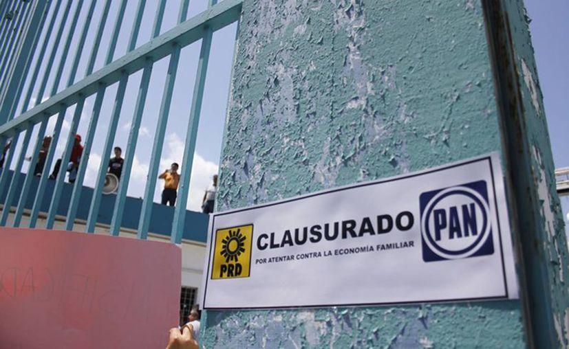 La multitud inconforme manifestaban su rechazó al incremento del transporte con megáfono y pancartas. (Susana Mariscal/SIPSE)