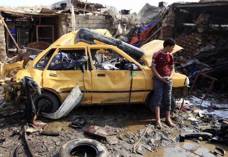 Un iraquí en la zona de un atentado con coche bomba cerca de Bagdad. (AP)