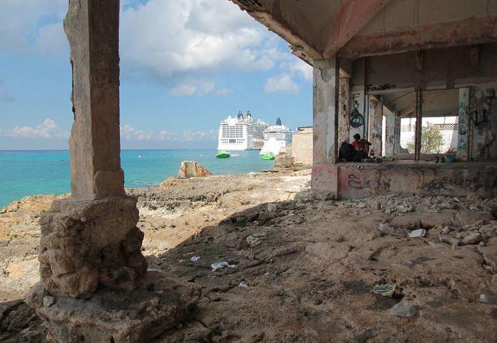 Las condiciones en las que los indigentes habitan las ruinas de un edificio, contrastan con la opulencia de los cruceros que arriban. (Gustavo Villegas/SIPSE)