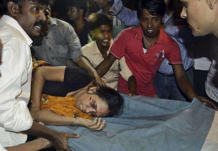 Una mujer es trasladada en camilla luego de una estampida durante un festival religioso en el este de India. (Agencias)