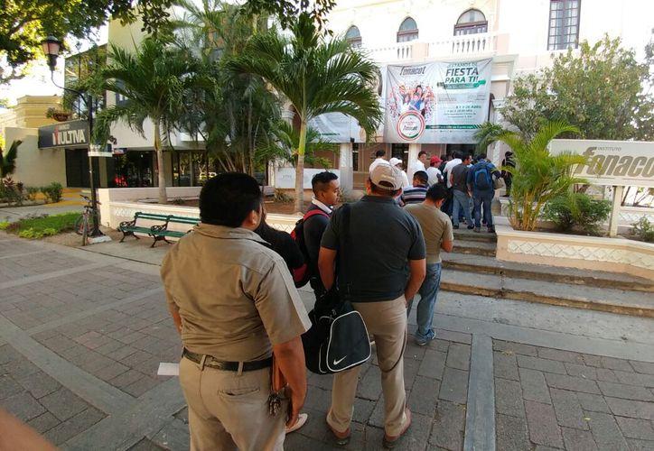 """Larga fila, que incluso """"obstruía"""" la ancha banqueta del Paseo de Montejo, se formó a las afueras de la delegación local de Fonacot; los trabajadores aseguraron que el problema se debió a los empleados, que los obligaron a hacer 2 veces la misma fila. (José Acosta/SIPSE)"""