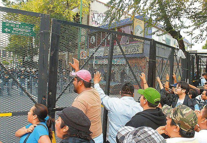 Los profesores intentaron llegar de nueva cuenta a gobernación, pero policías les impidieron el paso. (Milenio)