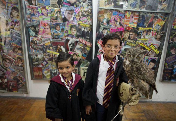 Mateo Lara, de cinco años, derecha, y su hermano Francisco,de siete, posan con un búho ante la colección más grande del mundo de artículos de Harry Potter,  que se exhibe en el Museo del Juguete Antiguo, en la Ciudad de México. (Agencias)
