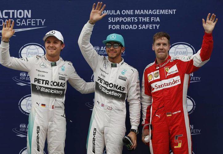 Tras lograr la pole en el Gran Premio de Malasia posa Lewis Hamilton (c), de la escudería Mercedes, con su coequipero Nico Rosberg (i) y el alemán de Ferrari, Sebastian Vettel. (Foto: AP)