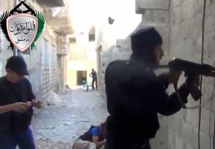 Rebeldes sirios durante un ataque contra fuerzas del gobierno de su país. (Agencias)