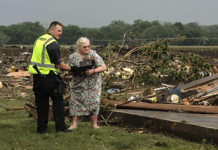 Una mujer es ayudada por un oficial tras el paso del tornado por Pilger. (Agencias)