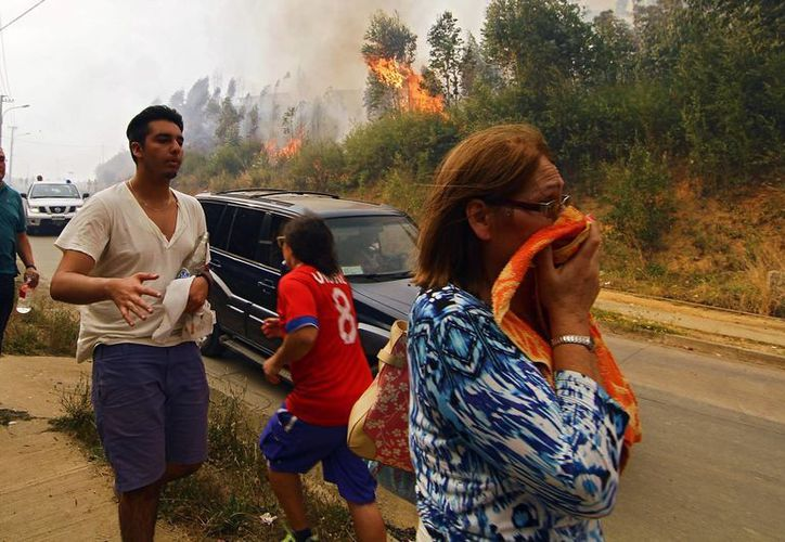 La gente reacciona ante el avance de un incendio forestal en Hualañe, una comunidad en Concepción, Chile. (Alejandro Zoñez/Aton vía AP)