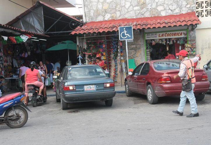 Automovilistas ocupan cajones para personas con problemas motrices. (Julián Miranda/SIPSE)