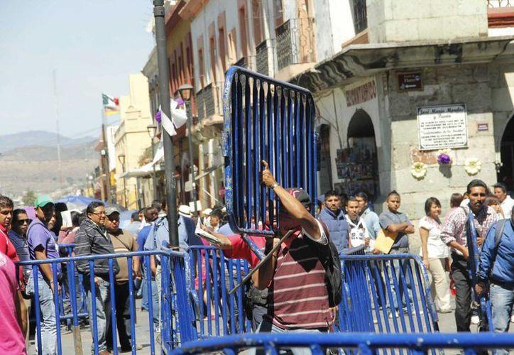 Maestros de la Sección 22 del SNTE en Oaxaca, derribaron con violencia las vallas que protegían al Palacio de Gobierno, para intentar ingresar a dialogar con las autoridades. (Archivo/Notimex)