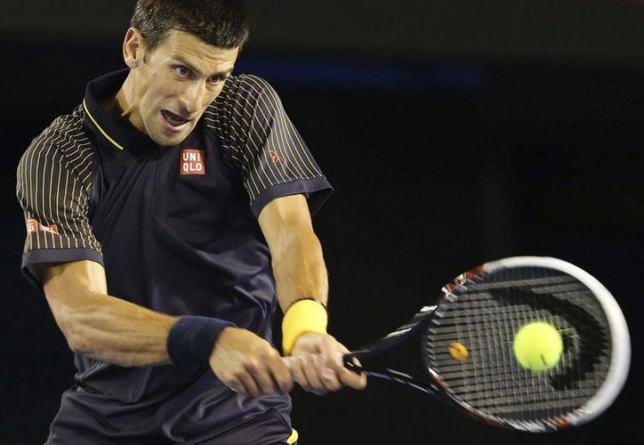 El tenista serbio Novak Djokovic devuelve la bola durante el partido que le enfrentó al estadounidense Ryan Harrison en el Abierto de Australia. (EFE)