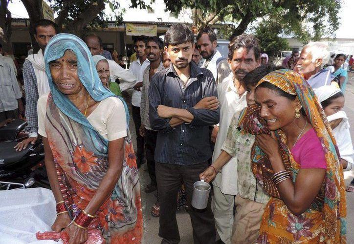 Familiares de las víctimas lloran tras la estampida registrada en un templo hindú en Madhya Pradesh, centro de la India, este lunes 25 de agosto de 2014. (EFE)